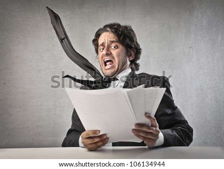 Scared businessman reading some documents - stock photo