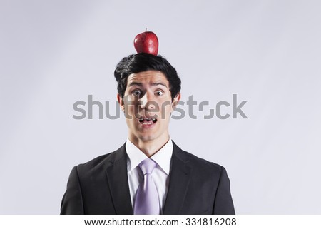 Scared businessman with a apple over his head - stock photo