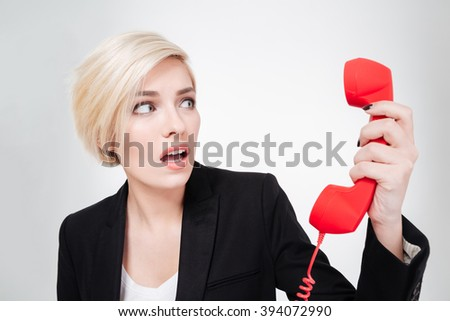 Scared businesswoman holding phone tube isolated on a white background - stock photo