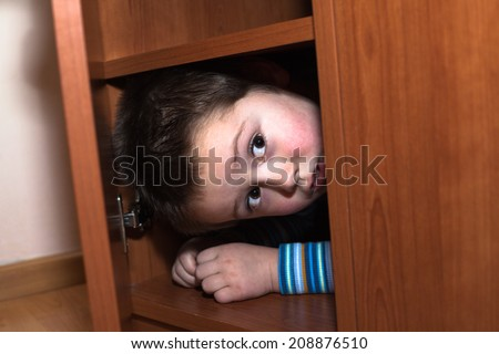 Scared child boy hiding in wardrobe - stock photo