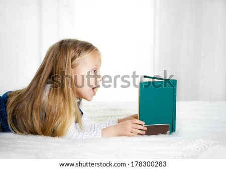 scared cute blonde haired school girl wearing a school uniform reading a book  lying on the bed