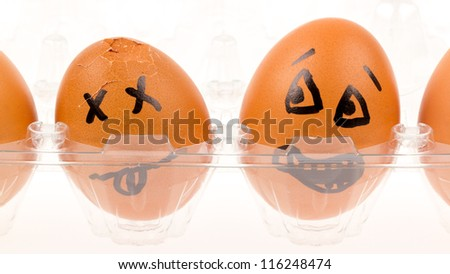 Scared egg looking at it's dead buddy, isolated - stock photo