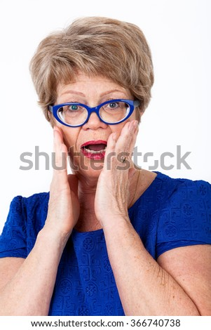 Scared elderly woman standing with wide opened eyes and mouth, covering her face, white background - stock photo