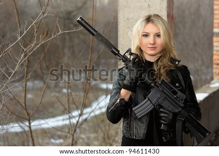 Scared girl in leather jacket with a big rifle - stock photo