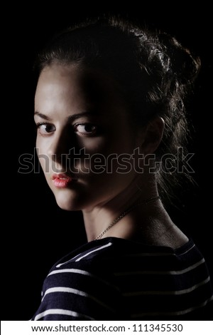 scared girl looking back on dark background - stock photo