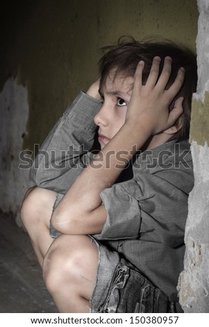 scared little boy in a dark cellar