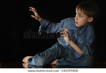 scared little boy on a black background - stock photo