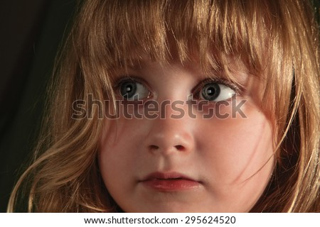 Scared look of very young girl with face expression over dark background - stock photo