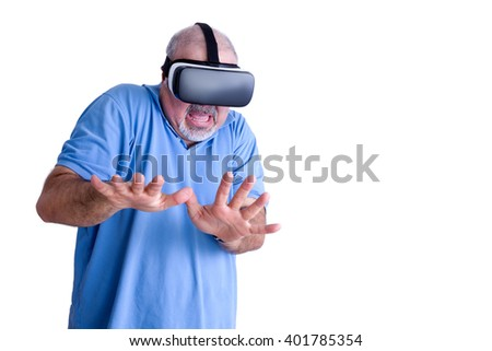 Scared man in blue shirt and wearing virtual reality glasses uses his hands to defend himself against an imagined attacker - stock photo