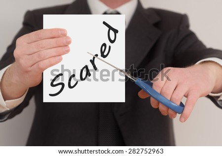 Scared, man in suit cutting text on paper with scissors