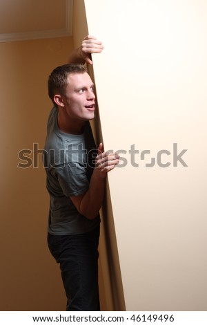 Scared Man Looking Around Corner - stock photo