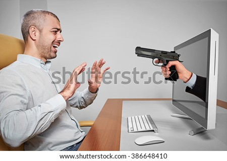 Scared man looks at hand holding a gun reaching out from a computer screen. - stock photo