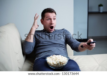 Scared man watching tv he is terrified. - stock photo