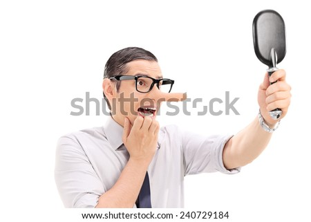 Scared man with long nose looking in a mirror isolated on white background - stock photo