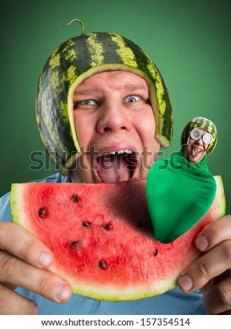 Scared man with watermelon helmet trying to eat slice with parasitic caterpillar in it - stock photo