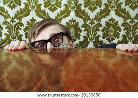 Scared nerd hiding behind a desk - stock photo