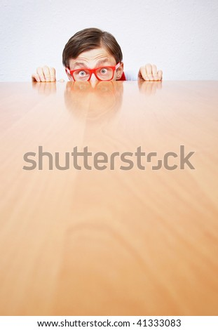 Scared nerd hiding behind a desk