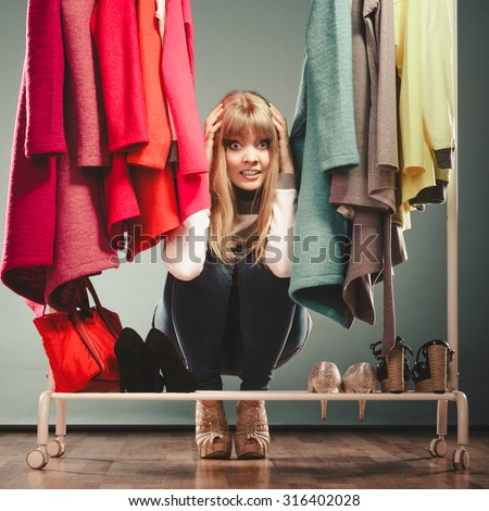 Scared pretty woman hiding among clothes in wardrobe. Attractive young girl customer shopping in mall shop. Fashion clothing sale concept. - stock photo