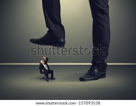 scared senior businessman under big leg his boss - stock photo