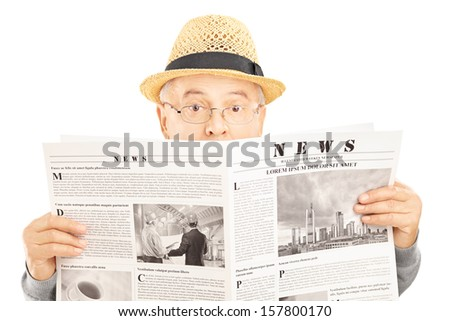 Scared senior man with glasses hiding behind a newspaper isolated on white background