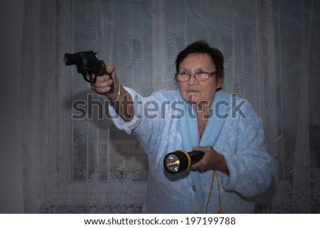 Scared senior woman aiming a gun and torch. - stock photo