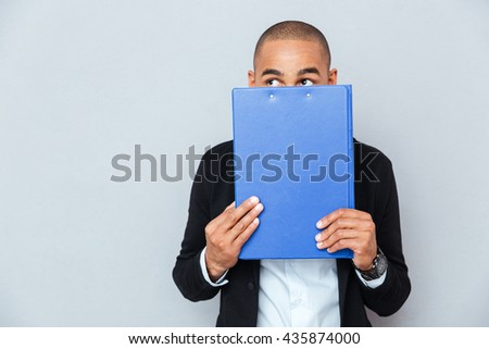 Scared shy african american young man covered his face with blue folder - stock photo