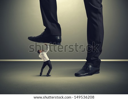 scared small businessman under big leg his boss - stock photo