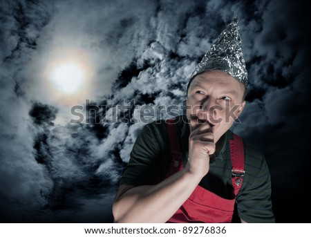 Scared suspecting man wearing a foil hat against dark stormy sky - stock photo