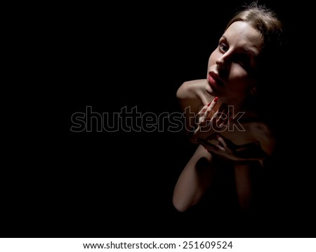 scared woman looking up in dark - stock photo