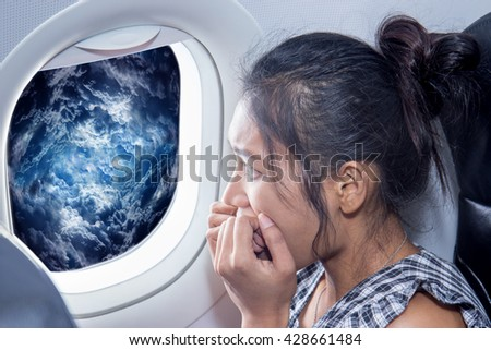 Scared woman looks at the clouds from an air plane window. Traveler looking out the airplane window on a raging storm. Passenger has a fear of plane crash. Woman on the aircraft looking at storm clouds.