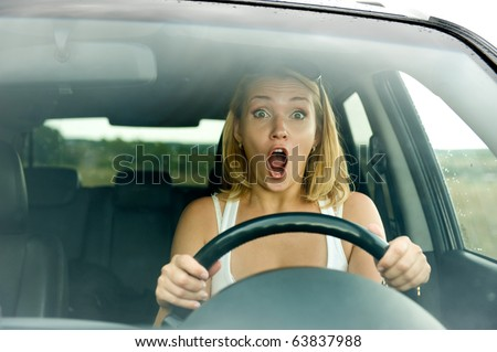 scared woman shouts driving the car - outdoors - stock photo