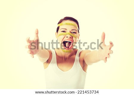 Scared woman with measuring tape on face