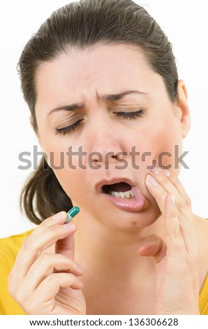 Scared woman with toothache holding a pill - stock photo