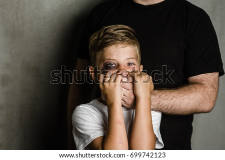 Scared young boy with an adult man's hand covering his mouth.