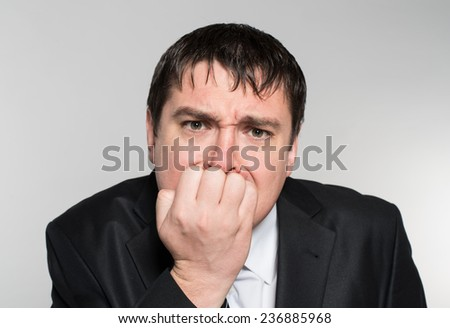 scared young business man biting his nails while looking into the camera. on a light gray studio background - stock photo