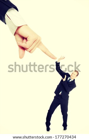 Scared young businessman afraid of big hand pointing on him, isolated on white - stock photo