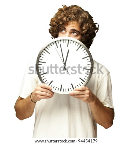 scared young man hidden behind a clock against a white background