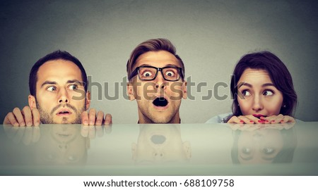 Scared young people two men and a woman hiding peeking form under the table