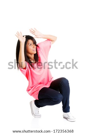 Scared young woman afraid of something above her, isolated on white  - stock photo