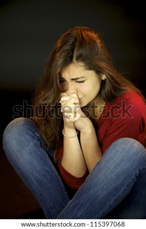Scared young woman crying and praying