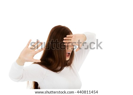 Scared young woman trying to hide and defend herself - stock photo