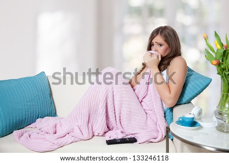 Scared young woman watching TV and hiding in blanket - stock photo