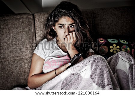 Scared young woman watching tv. Brunette girl sitting on couch with remote control - stock photo