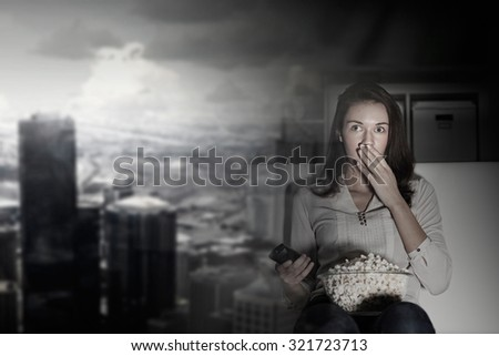 Scared young woman with click and popcorn watching TV