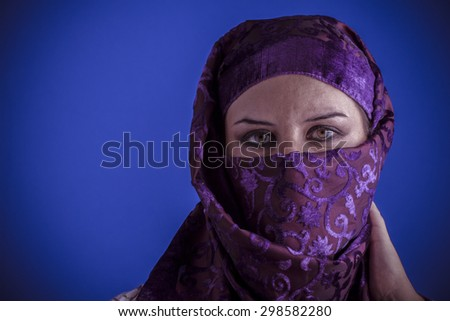 Scarf, Beautiful arabic woman with traditional veil on her face, intense look - stock photo
