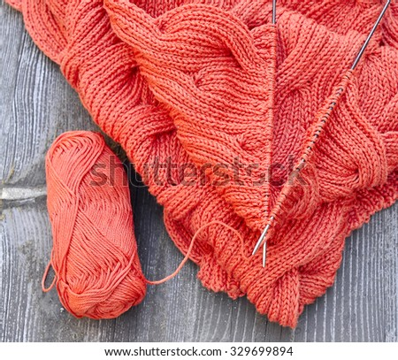 Scarf knitted from orange yarn with knitting needles and a ball on wooden background. - stock photo