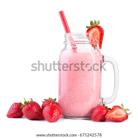 Scarlet strawberries are lying in front of a spacious glass jar with a handle. A jar with a handle is filled with a rose natural beautiful smoothie with a bright colorful red straw dipped in it.
