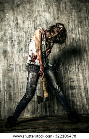 Scary bloody zombie girl with an ax. Halloween. - stock photo
