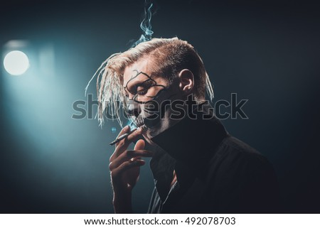 Scary boy with skull makeup smoking in the dark