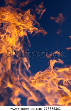 Scary bright hot orange yellow tongues of flame from a fire outdoor on clean blue sky background, vertical picture